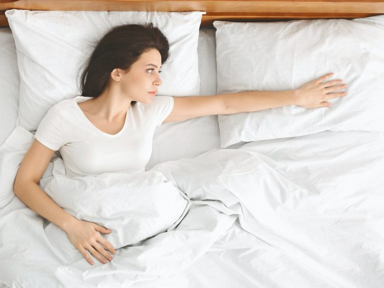 Depressed young woman lying in bed and feeling upset